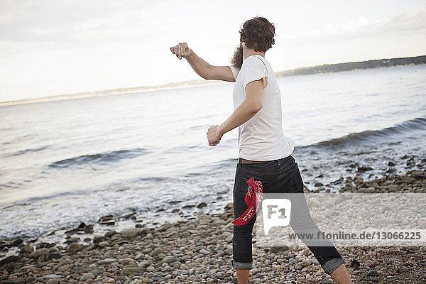 Rückansicht eines Mannes  der Steine ins Meer wirft