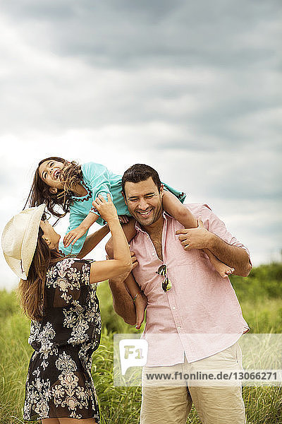 Cheerful parents playing with daughter on field against cloudy sky