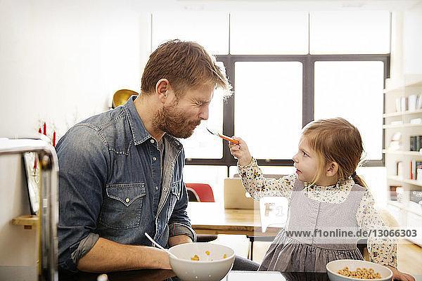 Tochter füttert Vater zu Hause
