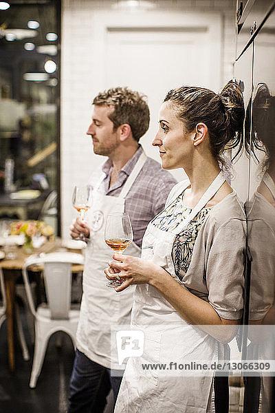 Mann und Frau halten Weinbrillen in der Hand  während sie an einer Großküche stehen