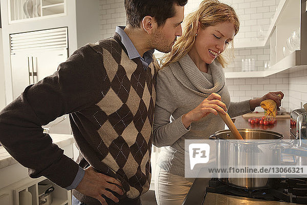 Man looking at woman cooking in kitchen