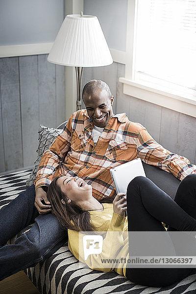 Fröhliches Paar entspannt zu Hause auf dem Sofa