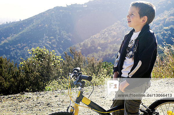 Boy looking away while sitting on bicycle
