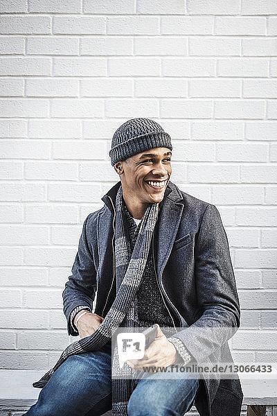 Glücklicher Mann schaut weg  während er an der Wand sitzt