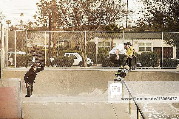 Friends skateboarding in park