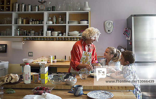 Woman talking with children while garnishing food in kitchen