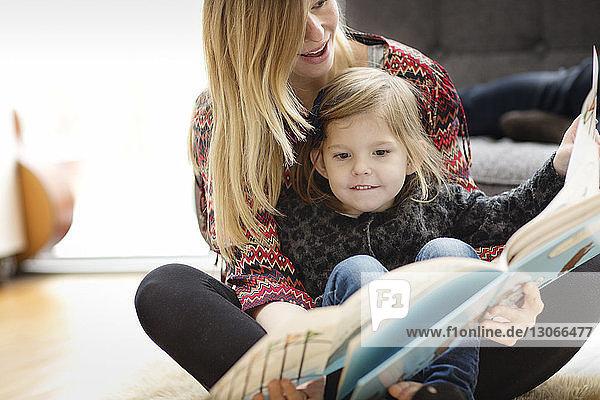 Mutter und Tochter schauen sich zu Hause ein Buch an