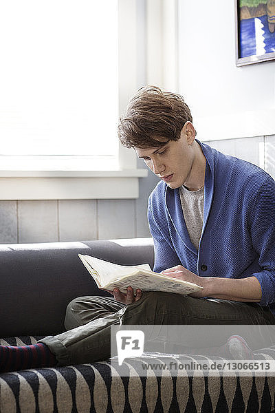 Man reading while sitting on sofa at home