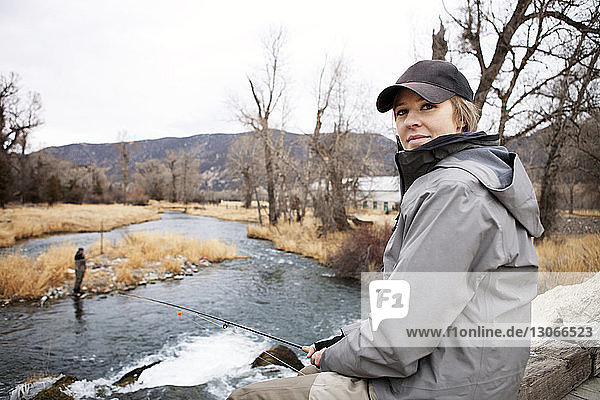 Woman fishing while sitting on footbridge