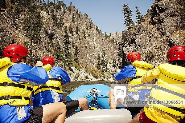 Rückansicht von Freunden beim Kajakfahren im Fluss gegen den Berg