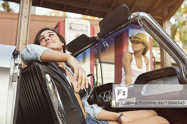 Frau sitzt im Auto  während ein Freund an der Zapfsäule steht