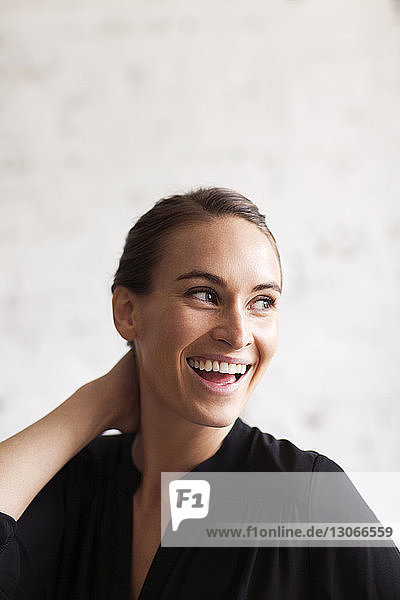 Cheerful woman looking away while standing against wall
