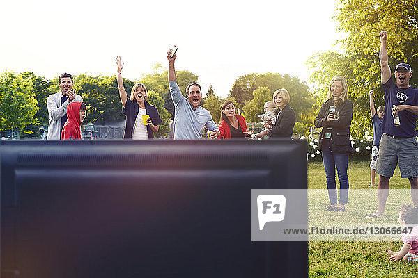 Familie feiert  während sie im Hinterhof fernsieht