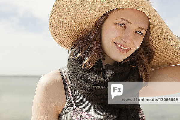 Portrait of smiling woman wearing sun hat against sky