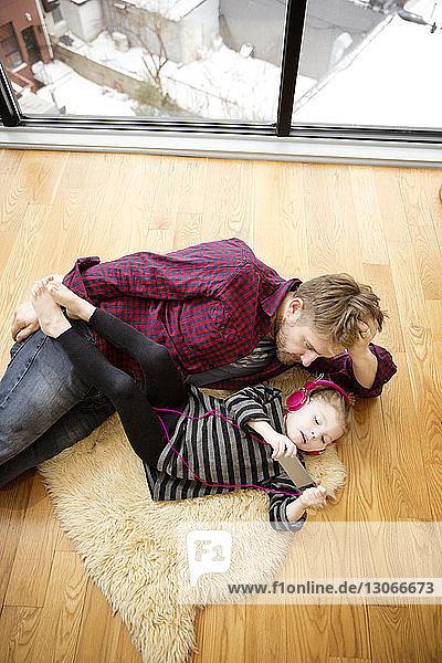 Hochwinkelansicht eines Mädchens  das Musik vom Vater hört  während es zu Hause auf dem Boden liegt