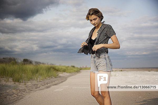 Frau hält Jacke  während sie auf der Straße gegen den Himmel steht
