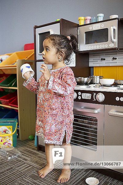 Girl holding cup while standing in kitchen at home