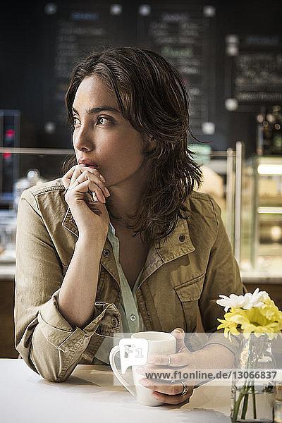 Nachdenkliche Frau mit Kaffeetasse sitzt am Tisch im Café