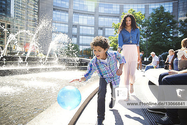 Playful boy with mother walking on footpath against building in city
