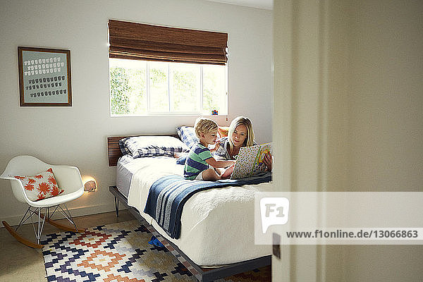 Woman showing book to son while relaxing on bed