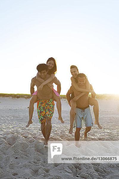 Men piggybacking women while walking on sand at beach
