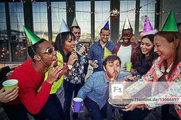 Mann bläst Kerzen auf einer Geburtstagstorte aus  die von einer Frau gehalten wird  während sie mit Freunden auf einer Party genießt