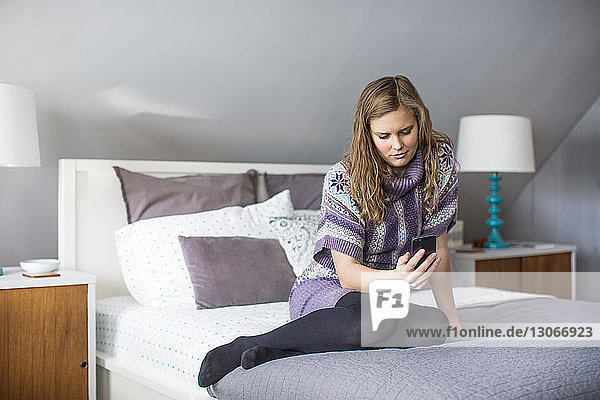 Woman using phone while sitting on bed at home