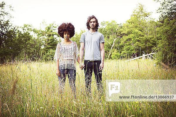 Porträt eines selbstbewussten Paares auf Grasfeld stehend