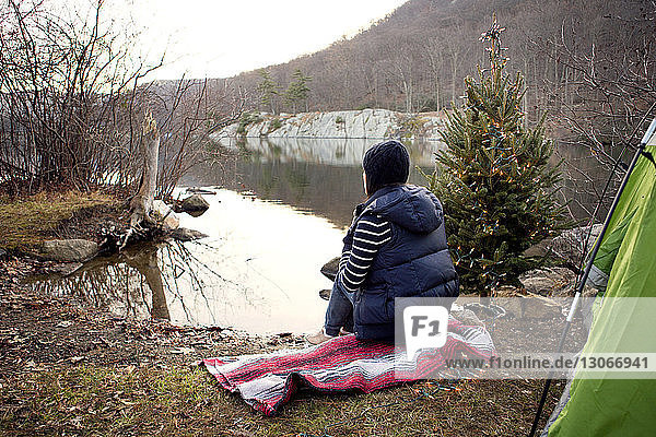 Woman sitting on towel at lakeshore by pine tree