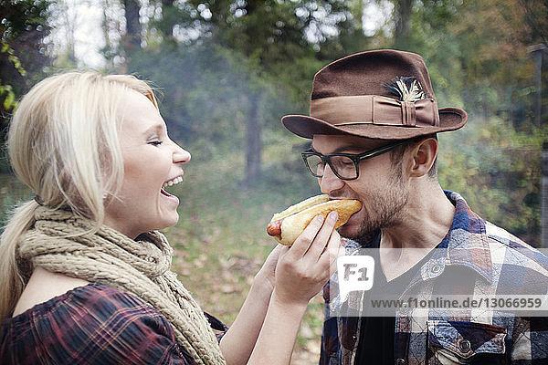 Frau füttert Mann  während sie im Hinterhof steht