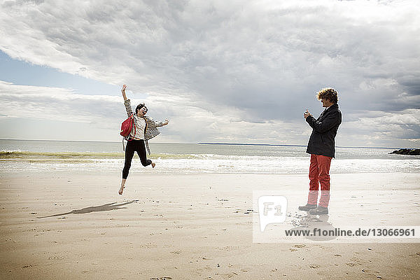 Man photographing jumping woman while standing on sand at beach