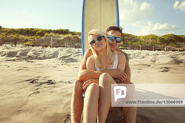Porträt eines romantischen Paares am Strand  das am Surfbrett sitzt