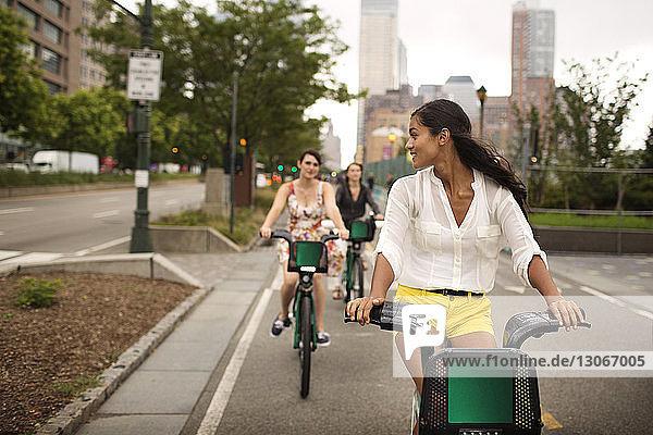 Freunde fahren Fahrrad auf Straße gegen Himmel
