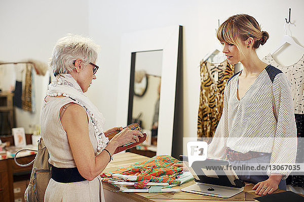 Ältere Frau bezahlt nach Einkauf in Boutique