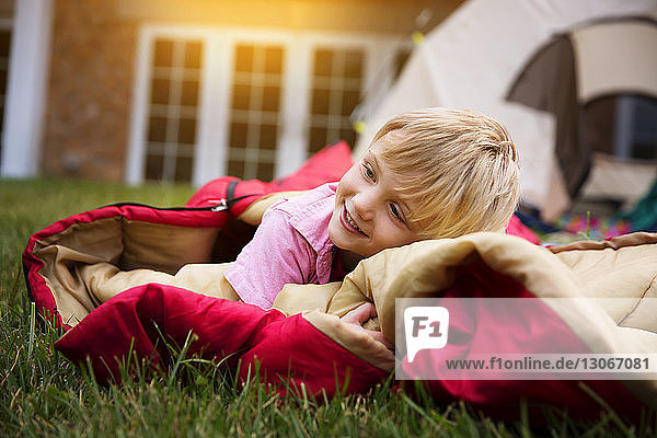 Smiling boy resting on sleeping bag against tent on grass in yard