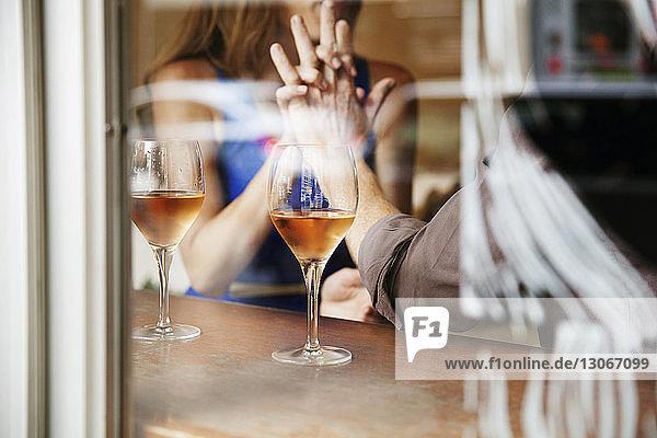 Paar  das im Restaurant durch ein Fenster gesehen Händchen hält