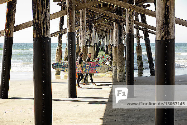 Friends carrying surfboard while walking below pier