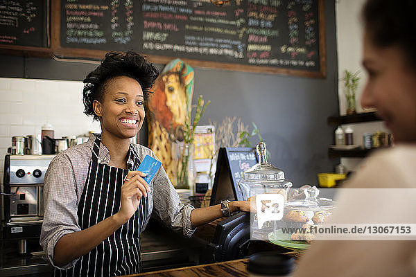 Happy woman holding debit card while looking at customer in cafe