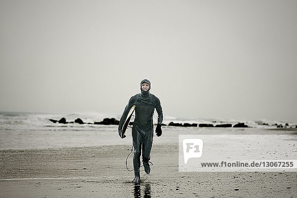 Portrait of man in wetsuit walking at beach against clear sky