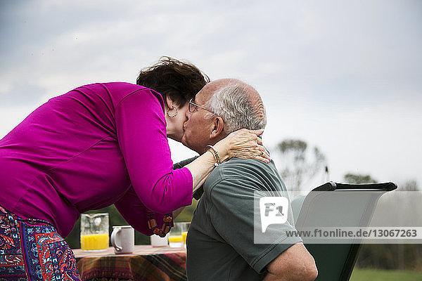 Seitenansicht eines älteren Mannes  der seine Frau küsst  während er am Tisch gegen den Himmel sitzt