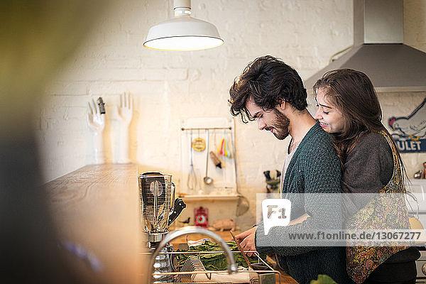 Seitenansicht eines in der Küche stehenden Paares