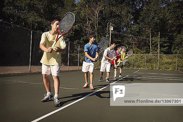 Players standing in row playing tennis at court