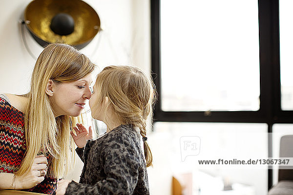 Mutter und Tochter reiben sich zu Hause die Nase