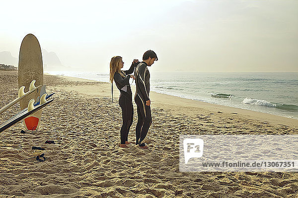 Woman assisting man in wearing wetsuit while standing at beach