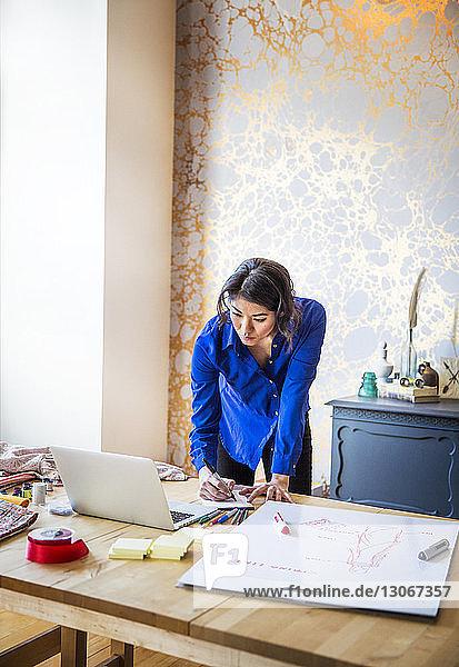 Zuversichtliche Frau  die im Büro arbeitet