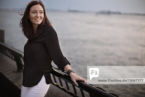 Smiling woman looking away while leaning on railing against lake
