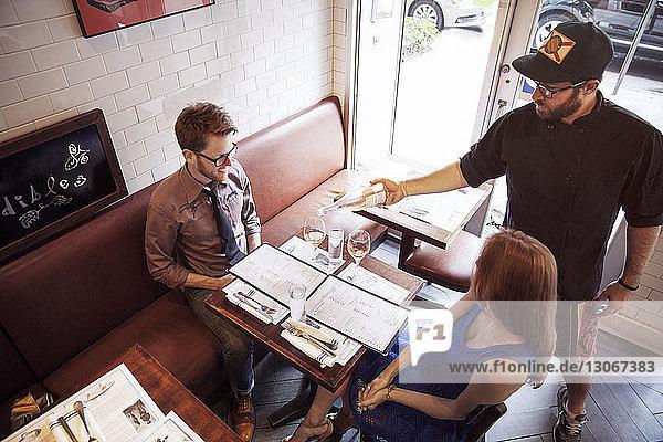 Kellner schenkt Wein ein für ein Paar  das im Restaurant sitzt
