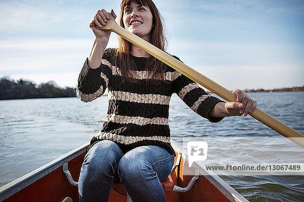 Lächelnde Frau rudert im Winter auf dem See gegen den Himmel