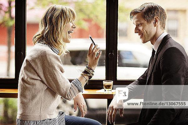 Glückliche Frau zeigt einem Mann ein Smartphone  während sie in einer Bar sitzt