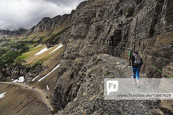 Rückansicht von Wanderern  die auf dem Berg gehen